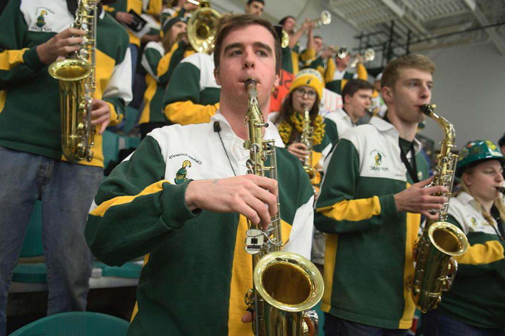 Clarkson Pep Band playing instruments at hockey game