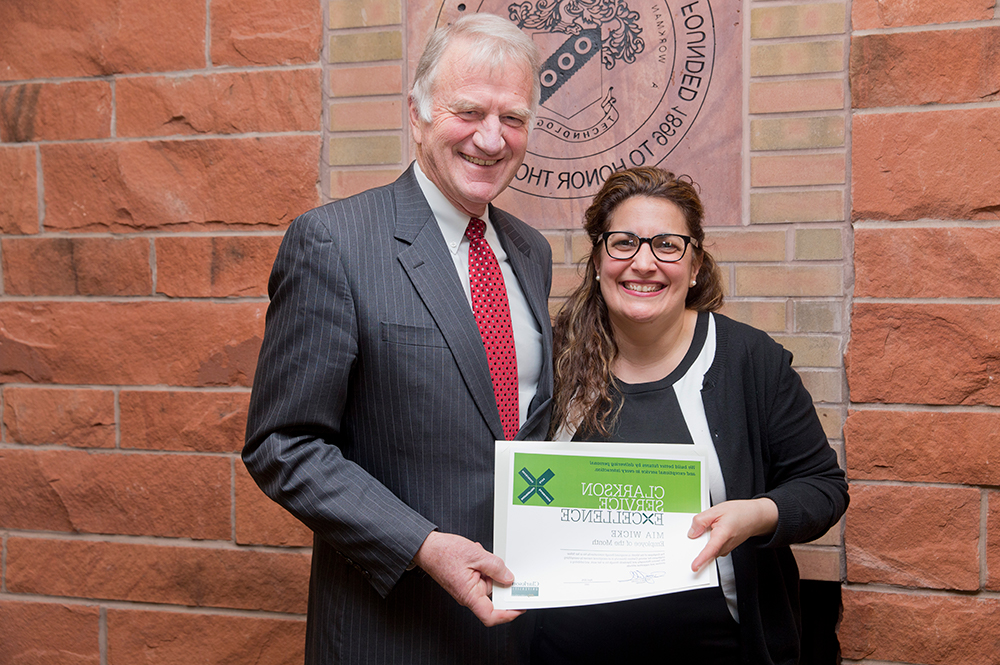 Employee Mia Wicke received Employee of the Month from President Tony Collins