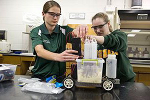 Two members of Clarkson's Chem E Car (Chem-E) 速度 Team work on their car for competition