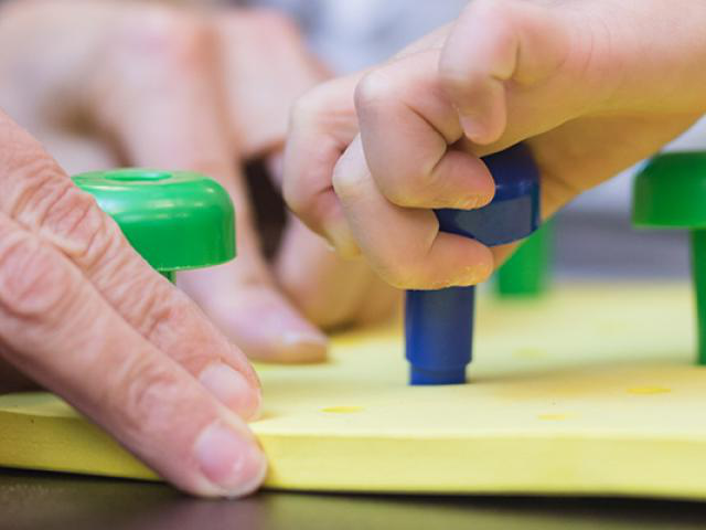 individuals placing pegs on a board for occupational therapy